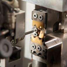 Zu sehen ist eine Maschine, welche Kunststoffkabel konfektioniert.